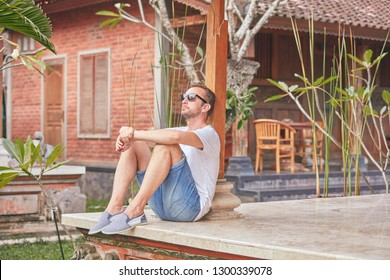 Man sitting on a house patio / porch and enjoying summertime.
