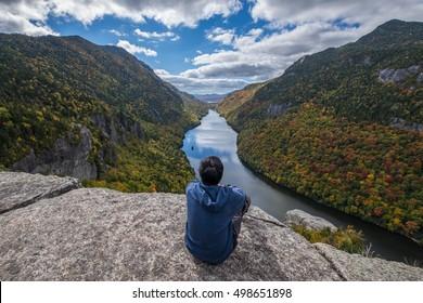 Man sitting on Indian Head Cliff at Adirondack Park, New York, USA.
