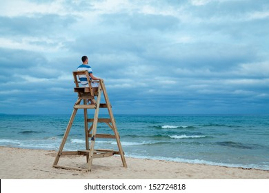 Man sitting on lifeguard chair, outdoor