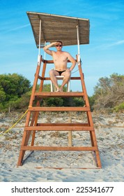 Man sitting on lifeguard tower on the beach.