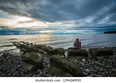 Man sitting on miracle beach in the Comox Valley, British Columbia, Canada