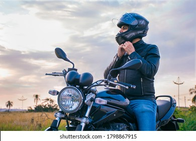 Man sitting on a motorcycle, wearing jeans and a black jacket, fastening his helmet with a landscape in the background. - Shutterstock ID 1798867915