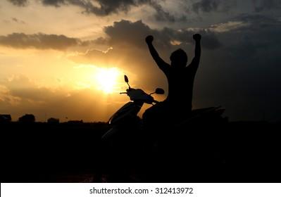 Man sitting on motorcycles sunset