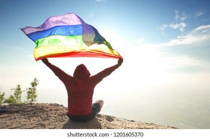 man sitting on mountain top raised rainbow LGBT symbol flag to bright sunny blue sky