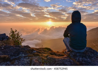 Man sitting on a mountain for watching Sunrise views alone,success and peace concept.