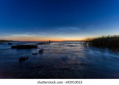 Man sitting on old broken jetty and gazing sunset
