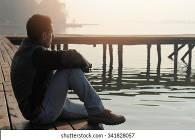 Man sitting on old wooden dock and looking at lake horizon. Thinking, contemplation  relaxing, concentration, loneliness concept