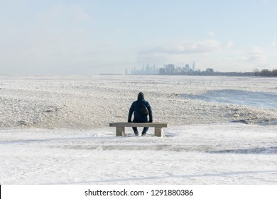 Man sitting on park bench on frozen lakeshore taking in the distant city skyline on a freezing winter day