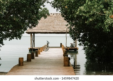 A man sitting on a pier next to his bicycle watching the sea