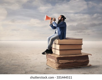 Man sitting on a pile of books screaming into a megaphone