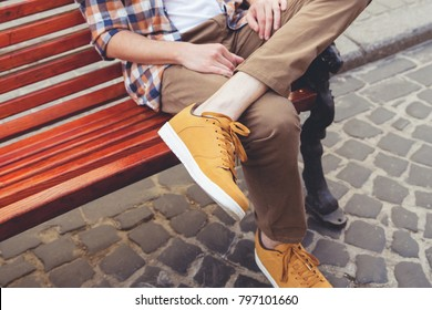 A man is sitting on the red bench in the city. Pose of introvert, closed personality. The guy in brown pants, checkered shirt and orange sneakers. Street fashion look, male fashion