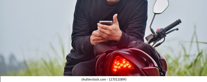 Man sitting on a red bike using his mobile phone isolated unique photo