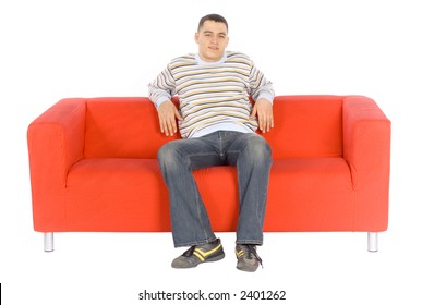 Man sitting on a red couch.  Isolated on white background, in studio.