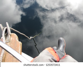 A man is sitting on the right side of the bow of a boat. The anchor rode is vanishing into the glassy water reflecting the clouds on the sky giving the illusion the rope is descending from the sky.
