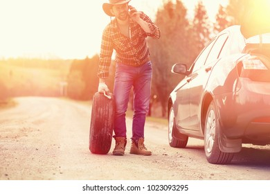 The man is sitting on the road by the car in the nature