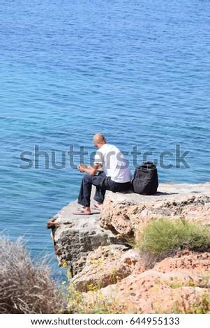 man sitting on rock facing sea stock photo edit now 644955133