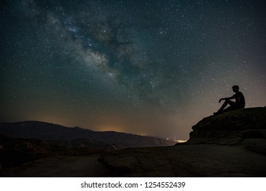 Man sitting on a rock looking at the stars with mountain landscape at night