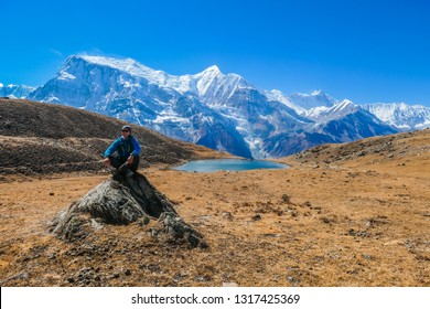 Man sitting on a rock, next to Ice lake, as part of the Annapurna Circuit Trek detour, Himalayas, Nepal. Annapurna chain in the back, covered with snow.  Dry grass, snowy peaks. Freedom and meditation