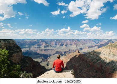 Man sitting on rock overlooking the Grand Canyon National Park on the South Rim whilst on outdoor summer vacation holiday in the US