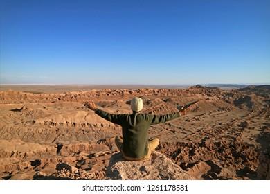 Man Sitting on the Rock Raising Arms Appreciating the Awesome view of the Moon Valley or Valle de la Luna, Atacama Desert, San Pedro Atacama, Chile