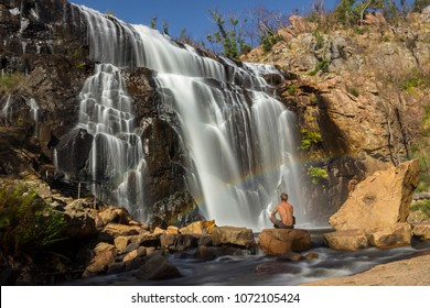 Man sitting on a rock under a Rainbow in front of waterfall, Mackenzie Falls, The Grampians, Australia