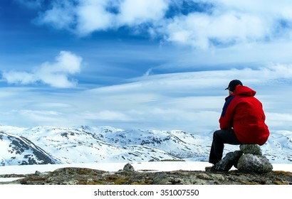 Man sitting on rocks and looking at the snow-covered hills. Blue sky with clouds. Norway