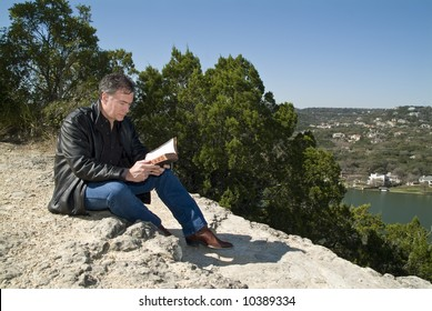 A man sitting on a rocky ledge reading a bible.