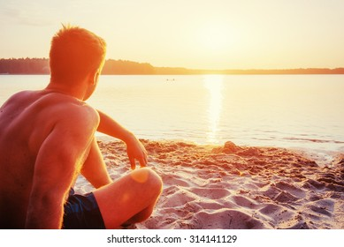 man sitting on the sand at sunset