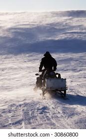 A man sitting on a snowmobile on a barren snow landscape