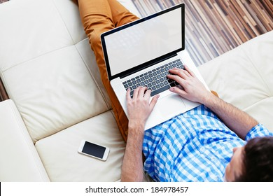 Man sitting on a sofa and browsing the web