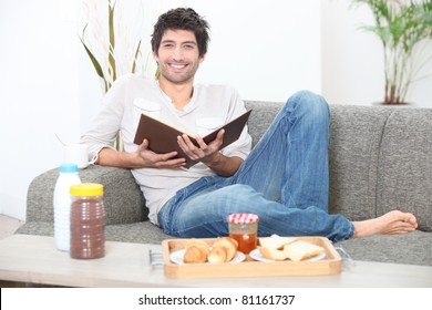 Man sitting on a sofa eating breakfast and reading a book