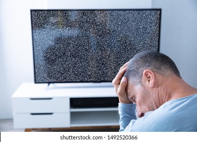 Man Sitting On Sofa In Front Of Television With No Signal
