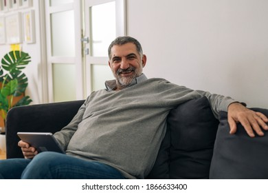 man sitting on sofa at his home and using digital tablet