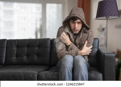 Man is sitting on sofa at home and feeling cold.