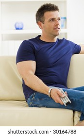 Man sitting on sofa watching TV at home.