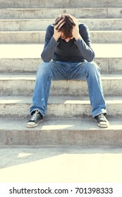 Man sitting on the stairs are saddened and frustrated with life./made picture to the concept. Toned photo.