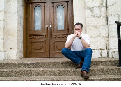 Man sitting on the steps of a church with an anxious expression on his face and in his body posture.