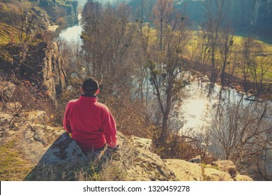 A man sitting on a stone above a beautiful mountain river in sunny autumn day. The man looking at water