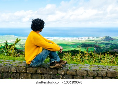 Man sitting on stone wall looking at coastal village in San Miguel, Azores Islands