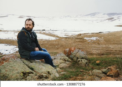 Man sitting on the stones and looking at winter nature view