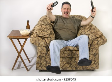 Man sitting on stuffed chair with TV remotes in hands and cheering