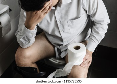 Man sitting on toilet bowl holding tissue paper  - health problem concept