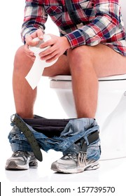 Man is sitting on the toilet bowl, holding paper in hands
