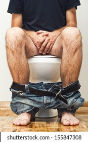Man sitting on toilet with his pants down.