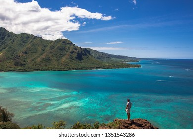 Man sitting on the top after hiking crouching lion and looking over the bay and beautiful view to mountain in Oahu, Hawaii.