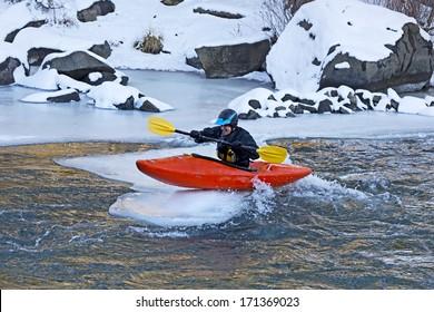 Man sitting on top of an ice flow in an orange kayak