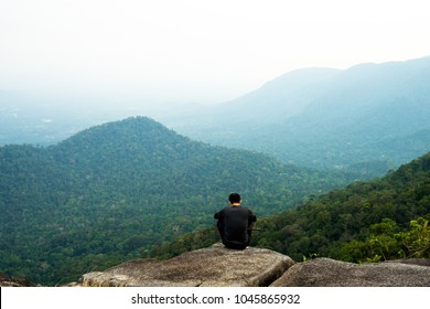 Man sitting on the top of the mountain in meditation session in Pha Hin Kup, Chanthaburi Thailand