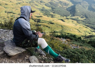 Man sitting on top of mountain.
