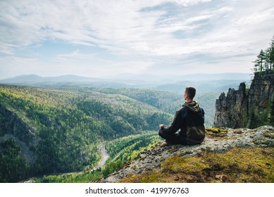 Man sitting on the top of the mountain in meditation session in Lotus Posture, padmasana, practicing pranayama, Freedom concept