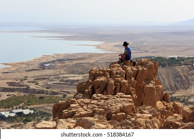 """Man is sitting on top of mountain and enjoying the dead sea landscape. Israel """"Ein Gedi"""" national park."""